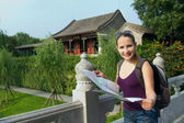 Caucasian woman with map and backpack travel in China — 图库照片