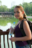 Portrait of young beautiful woman holding bottle of cold water — Stockfoto