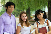Students holding books. Group of looking smiling together — Stock Photo