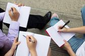 Teamwork of group holding pen and writing in book — Stock Photo