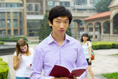 Portrait of young Asian man student carrying book and smiling — Stock Photo