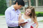 Male school teacher write and explain something to female studen — Stock Photo