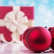 Christmas ball on abstract light background with gift box — Stock Photo