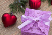 Decorated Christmas purple gift box with red ball and heart — Stock Photo