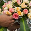 Arranging a bouquet of roses - Stock Photo