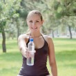 Woman holding a bottle of cold water in green park - Stock Photo