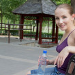 Woman resting in park after exercise. Sport fitness concept - Stock Photo