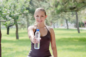 Woman holding a bottle of cold water in green park — Stock Photo