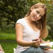 Young pretty female student with books working in a park — Stock Photo