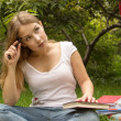 Portrait of college student with book thinking about exam — Stock Photo