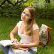 Stock Photo: Young womcollege student with book studing in park
