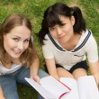 Happy university women student outdoor sitting on grass — Stock Photo
