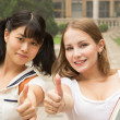 Students in park smiling and showing thumbs up success sign — Stock Photo