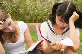 American and Asian students do homework outdoor of college — Stock Photo