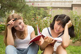 Happy caucasian and asian girl studying outdoor in university ca — Stock Photo