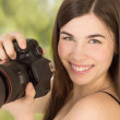 Closup portrait of woman photographer taking a photo with camera — Stock Photo