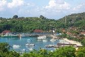 Lodě v chráněné zátoce s resort nebo vesnice — Stock fotografie