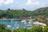 Pleasure boats in sheltered bay with resort or village — ストック写真