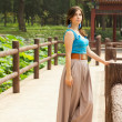 Young beauty woman in Chinese park with lotus pond — Stock Photo