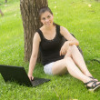 High school girl student do homework in the park on laptop — Stock fotografie