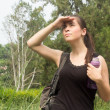 Backpacker womstanding in forest and looking to horizon — Stock Photo #31000177