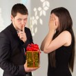 Man holds gift box for woman — Stock Photo