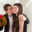 Man holding gift for woman and kissing her — Stok fotoğraf
