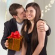 Young man hugging his girlfriend and offering gift — Стоковая фотография