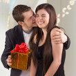 Young man hugging his girlfriend and offering gift — Stock fotografie