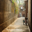 Old street with the brick wall and bicycle, lane of traditional — Stock Photo