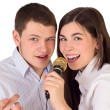 Friends singing in microphone at karaoke party and having fun — Stock Photo #35197277