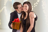Young man hugging his girlfriend and offering gift — Stock Photo