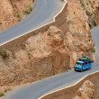 Overloaded car on a winding road — Stock Photo