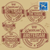 Grunge rubber stamp set with names of Netherlands cities — Stok Vektör