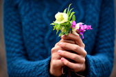 Girl hand giving flowers — Stock Photo