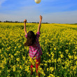 Young girl blowing bubble in a field of yellow flowers - Stock Photo