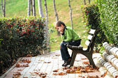 Sad boy sitting alone on a bench in a way — Stock Photo