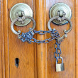 Old door knob and the door locked with chain — Stock Photo #30542661