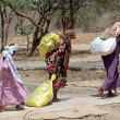 Stock Photo: Africwomen carrying help they receive to their homes