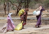 African women carrying the help they receive to their homes — Stock Photo