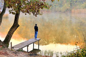 Autumn landscape reflected in the water facing the young — Stock Photo