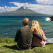 Young couple observe Volcano Mount Pico from the coast of Faial, Azores - Stock Photo