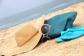 Blue beach bag on the seacoast and straw hat — Stock Photo