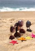 Four pairs of sunglasses on the beach — Stock Photo