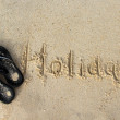 Word Holiday written on the wet sand — Stock Photo