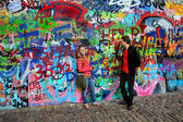 John Lennon wall in Prague and young beautiful couple in love — Stock Photo