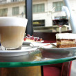 Latte and tiramisu in Parisian cafe - Stock Photo