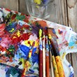 Art palette, tubes with paints and paintbrushes — Stock Photo #30043491