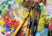 Beautiful vivid art palette and mix of paintbrushes — Stock Photo