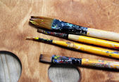 Beautiful wooden art palette and mix of paintbrushes — Stockfoto